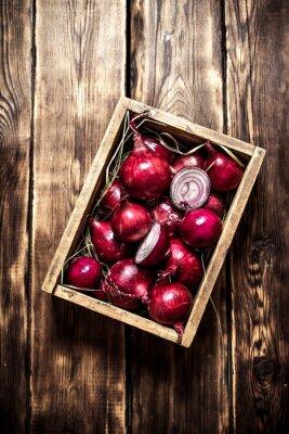 Плакат Свежий красный лук в старом ящике.