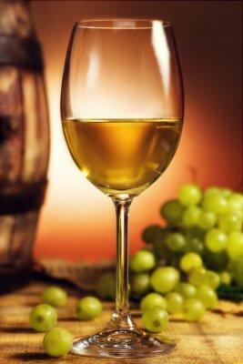 Плакат Бокал белого вина перед зеленым виноградом и старой бочке