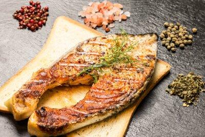 Плакат приготовленные на гриле филе лосося над горячей ломтик хлеба и специй над шифера
