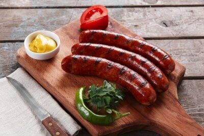 Плакат Жареная колбаса на деревянной доске с соусом и овощами