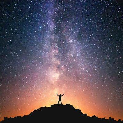 Плакат Человек и Вселенная. Человек, стоящий на вершине холма рядом с галактики Млечный Путь с поднятыми руками в воздухе.
