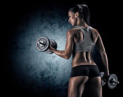 Плакат Мышечная женщина в студии на темном фоне