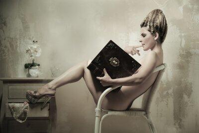 Плакат Обнаженная женщина, сидя в кресле, читая книгу в помещении
