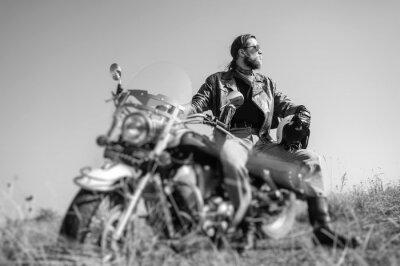 Плакат Портрет молодого человека с бородой сидит на своем мотоцикле и крейсерской глядя на солнце. Человек носить кожаную куртку и синие джинсы. Низкая точка зрения. Наклон линзы эффект размытия. Черное и бе