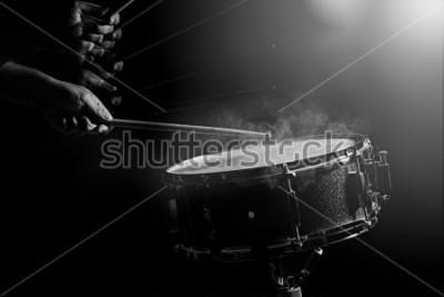 Плакат Человек играет малый барабан на фоне слабого света.