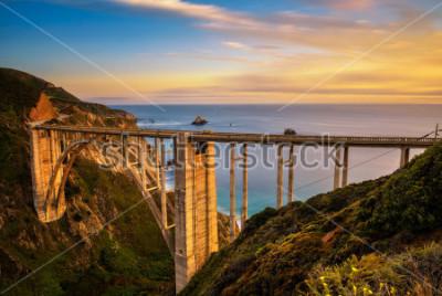 Плакат Мост Биксби (Rocky Creek Bridge) и шоссе Тихоокеанского побережья на закате возле Big Sur в Калифорнии, США. Длительное воздействие.
