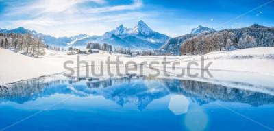 Плакат Панорамный вид на красивые белые зимние пейзажи страны чудес в Альпах со снежными вершинами гор, отражающиеся в кристально чистом горном озере в холодный солнечный день с голубым небом и облаками