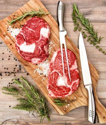 Плакат Сырье свежее мясо Рибай стейк с травами и специями на деревянный стол