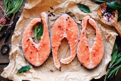 Плакат Сырье стейки из лосося со свежей зеленью, солью и перцем мозолей. вид сверху