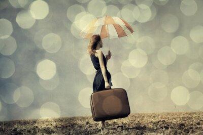 Плакат Рыжая девушка с зонтиком и чемоданом в ветреную области