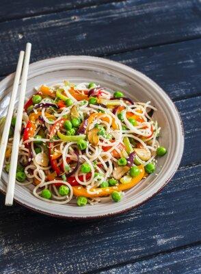 Плакат Рисовая лапша с овощами обжаривают на керамической пластине на темном деревянном фоне