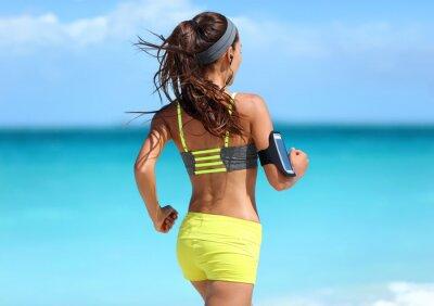 Плакат Запуск мотивации - бегун тренировки с музыкой видно из-за бега трусцой в моде желтый спортивный бюстгальтер ремни и неоновые шорты наряд носить беспроводные наушники на пляже летом фоне.