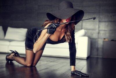 Плакат Сексуальная женщина в шляпу и кнут на коленях на полу в помещении