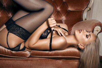 Плакат сексуальная женщина в черном белье соблазнительной лежа на диване в чулках