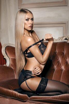 Плакат сексуальная женщина в соблазнительной черный белье, сидя на диване в чулках