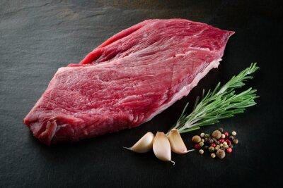Плакат Кусочек сырой говядины с пряностями на темном фоне