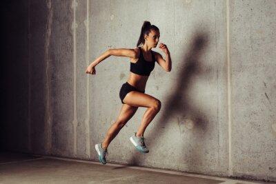 Плакат Тонкий привлекательной спортсменкой работает на бетонную фоне