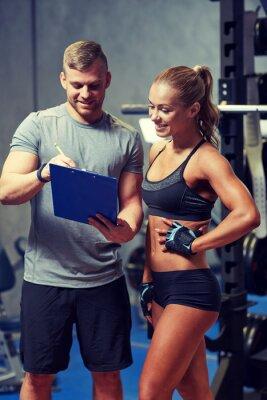 Плакат улыбается молодая женщина с личным тренером в тренажерном зале