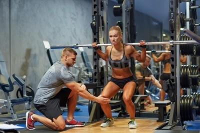 Плакат спорт, фитнес, работа в команде, бодибилдинг и люди концепции - молодая женщина и личный тренер с штангой сгибание мышц в тренажерном зале