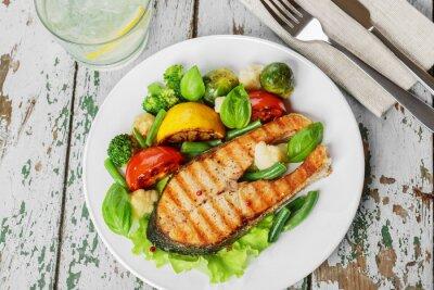 Плакат стейк на гриле лосось с овощами на тарелке
