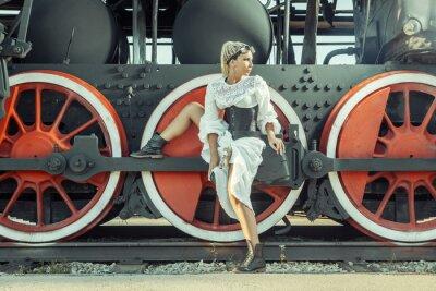 Плакат Женщина в винтажном платье сидит на колесе локомотива.