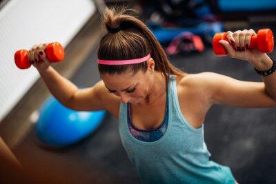 Плакат Женщина поднятие тяжестей и работает на ее плечи в тренажерном зале