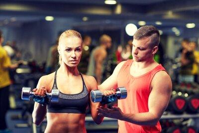 Плакат молодая пара с гантелями сгибая мышцы в тренажерном зале