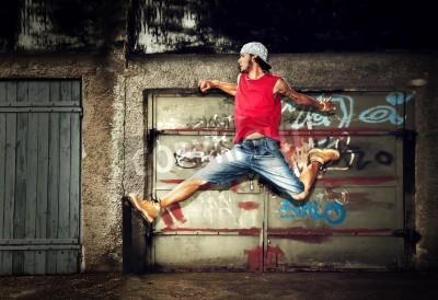 Плакат Молодой человек прыгает / танцы на фоне гранж граффити стены