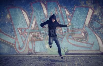 Плакат Молодой человек прыгает с граффити в фоновом режиме