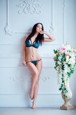 Плакат Молодая, сексуальная женщина с горячим телом позирует в нижнем белье на роскошный интерьер близко к цветам.