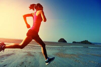 Плакат young woman running on sunrise beach