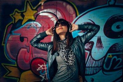 Плакат Молодая женщина с наушниками, наслаждаясь музыкой