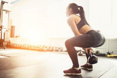 Наклейка Атлетик женщина, осуществляющих с чайник колокол во время пребывания на корточках позиции. Мышечная женщина делает CrossFit тренировки в тренажерном зале.