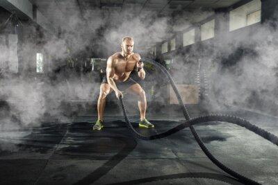 Наклейка Атлетический молодой человек с веревкой сражения делая тренировку в спортзале фитнеса. Спортивная концепция.