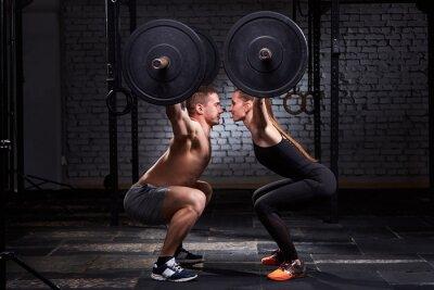 Наклейка Crossfit подъема бар женщина и мужчина в групповой тренировки против кирпичной стены.