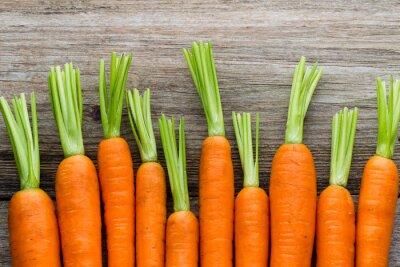 Наклейка Свежая морковь кучу на деревенском деревянном фоне.