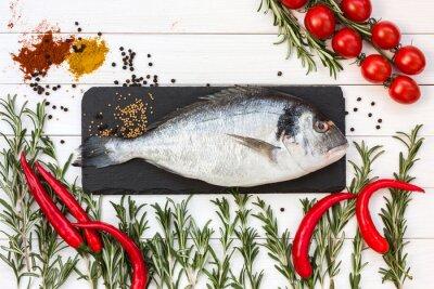 Наклейка Свежая рыба дорадо, розмарин, помидоры черри, перец чили на белом деревянный стол. Вид сверху.