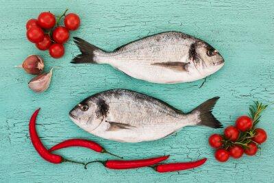 Наклейка Свежая дорадо рыба с овощами на синем столе. Копирование пространства, вид сверху