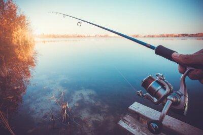 Наклейка рука с прядения и бобины на вечернем летнем озере