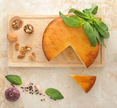 Наклейка глава копченого сыра сулугуни на деревянной доске с грецкими орехами и