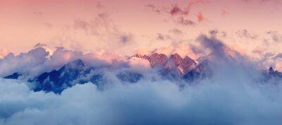 Наклейка Высокая горная цепь в облаках во время восхода солнца. Красивый панорамный пейзаж