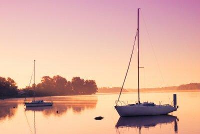 Наклейка Маленькие парусные лодки отразить в спокойной воде во время восхода солнца.