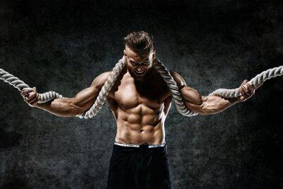 Наклейка Мускулистый мужчина с веревкой. Фотография человека с совершенным телом после тренировки. Модный стиль