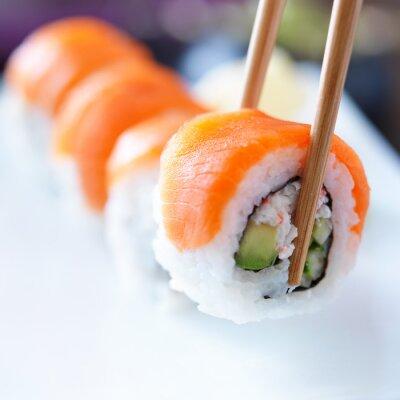 Наклейка поднимая кусок суши с палочками для еды
