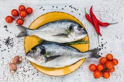 Наклейка Сырая свежая рыба дорадо на желтой табличке и овощами на белом столе. Вид сверху.