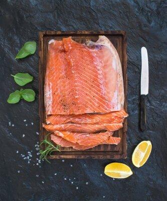 Наклейка Копченая филе лосося с лимоном, свежими травами и разводят на деревянной доске над сервировки темном фоне каменной
