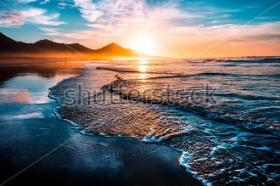 Наклейка Удивительный пляжный закат с бесконечными горизонтами и одинокими фигурами на расстоянии и невероятными пенистыми волнами. Вулканические холмы на заднем плане.
