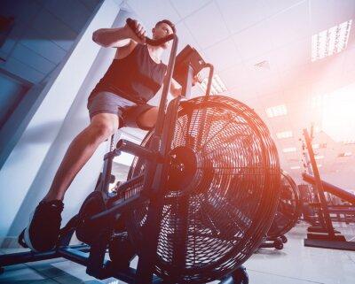 Наклейка Молодые человеки с мышечным телом используя воздушный велосипед для cardio разминки на спортзале перекрестной тренировки.